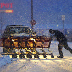 George Zamfir pushes Target shopping carts back to the store with heavy snowflakes accumulating to the ground Monday evening during the rush hour commute home.
