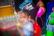 "13 APRIL 2013 - BANGKOK, THAILAND:  A Thai boy participates in a water fight on Khao San Road, which is Bangkok's ""backpacker"" district, during Songkran celebrations in the Thai capital. Songkran is celebrated in Thailand as the traditional New Year's Day from 13 to 16 April. The date of the festival was originally set by astrological calculation, but it is now fixed. If the days fall on a weekend, the missed days are taken on the weekdays immediately following. Songkran is in the hottest time of the year in Thailand, at the end of the dry season and provides an excuse for people to cool off in friendly water fights that take place throughout the country. Songkran has been a national holiday since 1940, when Thailand moved the first day of the year to January 1.   PHOTO BY JACK KURTZ"