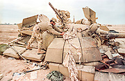 A Qatar soldier examines a destroyed Iraqi T-55 battle tank during clean up operations following the Battle of Khafji February 2, 1991 in Khafji City, Saudi Arabia. The Battle of Khafji was the first major ground engagement of the Gulf War.