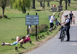 © Licensed to London News Pictures. 11/04/2020. London, UK. A Police cyclists patrolling Richmond Park questions two people lying on the grass in the park during the Easter Bank holiday where temperatures are expected to reach 26c. People have been told to stay at home and only leave homes to exercise or when absolutely essential in an attempt to fight the spread of COVID-19 the coronavirus disease. Photo credit: Alex Lentati/LNP