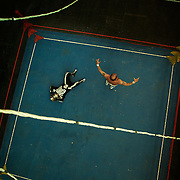 Wrestler Gran Mortis, dressed in a skeleton outfit, lies prone on the canvas after his defeat to Veteran 'campeon Legendario' Mister Atlas during the 'Titans of the Ring' wrestling group's Sunday performance at El Alto's Multifunctional Centre. Bolivia. The wrestling group includes the fighting Cholitas, a group of Indigenous Female Lucha Libra wrestlers who fight the men as well as each other for just a few dollars appearance money. El Alto, Bolivia, 14th March 2010. Photo Tim Clayton