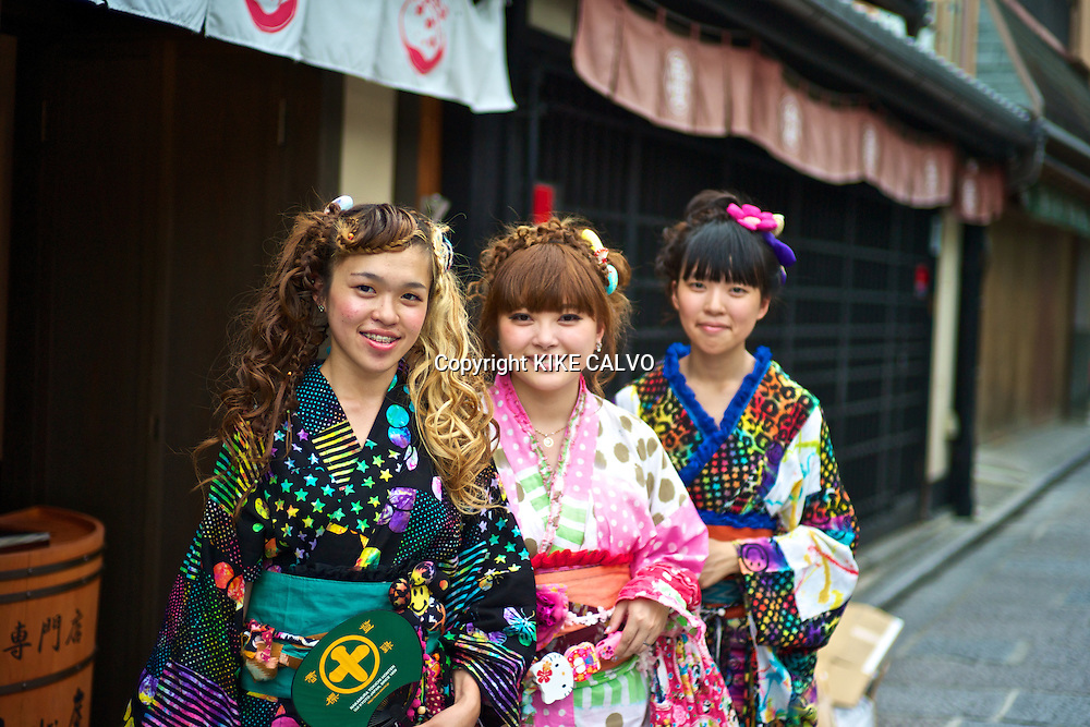 Asian teens wearing a modern colorful version of the traditional kimonos explore the stores and shops near the Kiyomizu Temple.