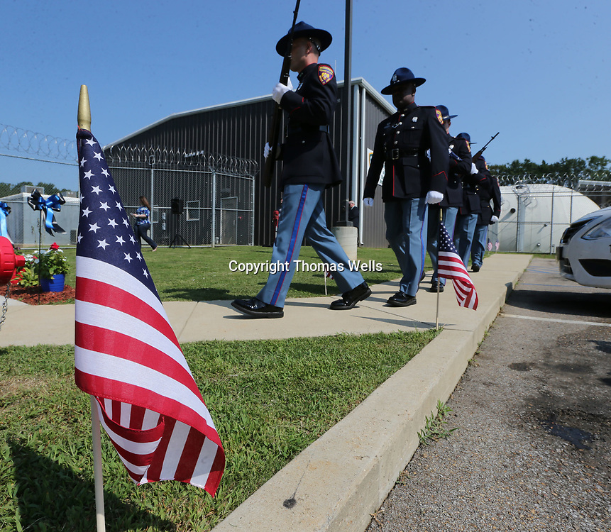 Small American flags line the sidewalk as the Mississippi Highway patrol Honot Guard make their way to the flagpole at the Tishomingo County Sheriff's Department to dedicate a flag for MBN Officer Lee Tartt who was killed during a 2016 standoff.