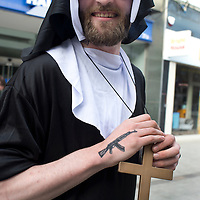 Bognor Regis, Sussex. Young man on a stag do wearing a nun's habit , with kalashnikov tattoo and large wooden crucifix.
