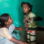 CAPTION: Sushma has a form of cerebral palsy called diplegia. She needs almost constant care. During the earliest days following the birth of a child who has (or develops) a disability, parents often struggle to work out what best they can do for him or her, and could use more information and firmer direction. Under the Chamkol programme, such children aged between zero and five and their mothers, expectant mothers and women of child-bearing age will be able to get this through health, wellbeing, development and pre-school programmes run through Early Years' Clubs. LOCATION: Mangala (village), Kasaba (hobli), Chamrajnagar (district), Karnataka (state), India. INDIVIDUAL(S) PHOTOGRAPHED: Ambika (left) and Sushma (right).