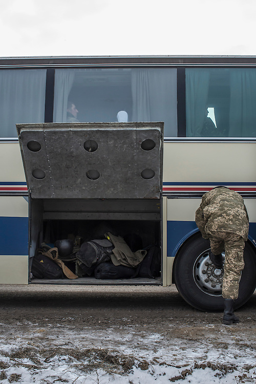 ARTEMIVSK, UKRAINE - FEBRUARY 19: Ukrainian soldiers from a unit based in Zaporizhia board a bus for further transport after withdrawing from Debaltseve on February 19, 2015 in Artemivsk, Ukraine. Ukrainian forces started withdrawing from the strategic and hard-fought town of Debaltseve yesterday being effectively surrounded by pro-Russian rebels. (Photo by Brendan Hoffman/Getty Images) *** Local Caption ***