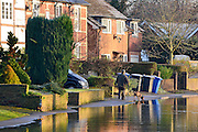 © Licensed to London News Pictures. 12/01/2014. Wraysbury, UK. A man and a dog walk along a flooded pavement. Flooding in Wraysbury, Berkshire today 12th January 2014.  Flooding and property damage is expected to continue along the River Thames.  Large areas of Britain are experiencing flooding after wet weather. Photo credit : Stephen Simpson/LNP