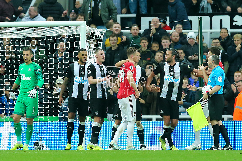Scott McTominay (#39) of Manchester United and Andy Carroll (#7) of Newcastle United are pulled apart following the Premier League match between Newcastle United and Manchester United at St. James's Park, Newcastle, England on 6 October 2019.