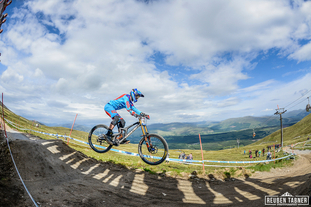 Max Morgan grabs some air whilst crowds watch from above at the top of the Fort WIlliam downhill track during Saturday practise at the UCI Mountain Bike World Cup.