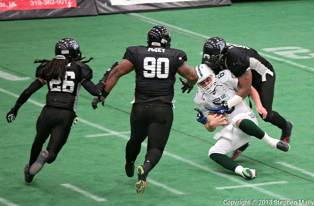 Cedar Rapids Titans defensive lineman Xzavie Jackson (93) sacks Green Bay Blizzard quarterback Spencer Ohm (6) as defensive back Donald Smith (26) and defensive lineman Richard Posey (90) close in during their game at the Cedar Rapids Ice Arena in Cedar Rapids on Saturday, June 8, 2013.