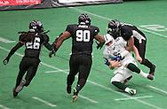 Cedar Rapids Titans defensive lineman Xzavie Jackson (93) sacks Green Bay Blizzard quarterback Spencer Ohm (6) as defensive back Donald Smith (26) and defensive lineman Richard Posey (90) close in during their game at the Cedar Rapids Ice Arena in Cedar Rapids on Saturday, June 8, 2013.