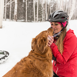 A woman and her dog take a break while fat tire biking on a snowy winter day in New Hampshire's White Mountains.