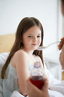 Mother preparing cough syrup for daughter in bedroom