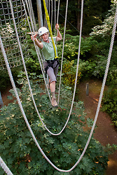 United States, Bellevue, woman walking across ropes at Discovery Challenge Ropes Course.  MR