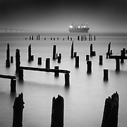 Refuge, Columbia River, Astoria.  A ship in transit waits out a winter storm as it lashes the Astoria waterfront with rain squalls.  These hundred-year-old pilings once supported a thriving fish processing and packing industry, Astoria, Oregon, USA.