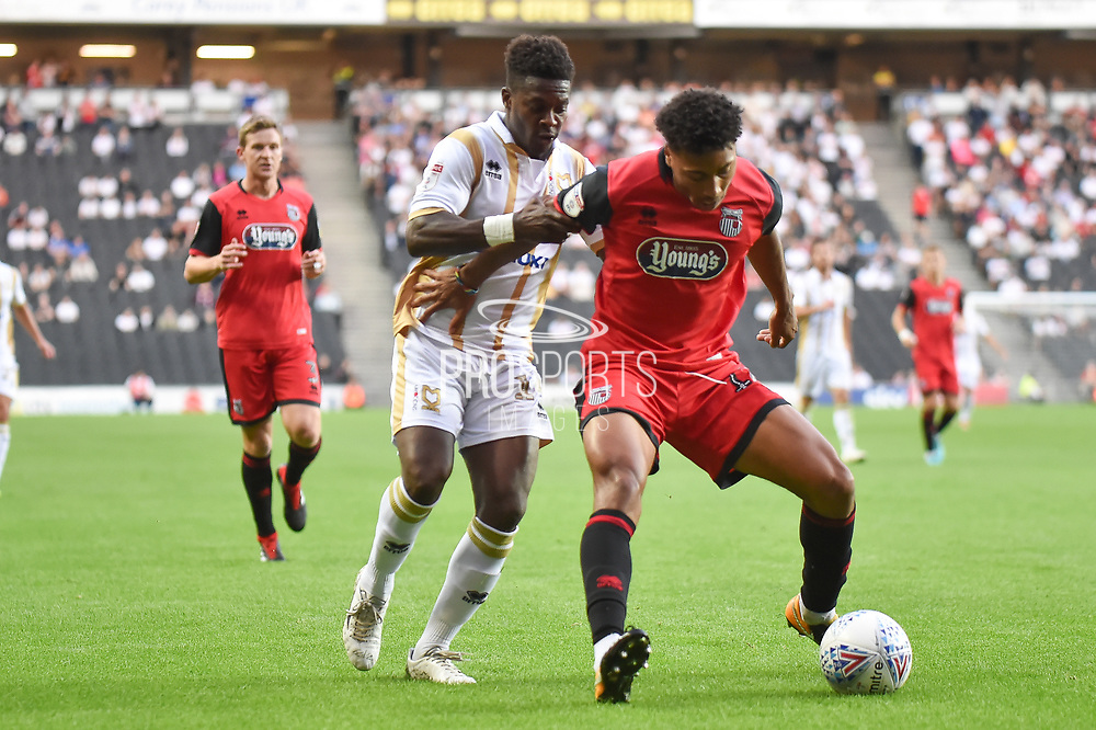 Milton Keynes Dons striker Kieran Agard (14) and Grimsby Town defender (on loan from Luton Town) Akin Femewo (12) chase down the ball during the EFL Sky Bet League 2 match between Milton Keynes Dons and Grimsby Town FC at stadium:mk, Milton Keynes, England on 21 August 2018.