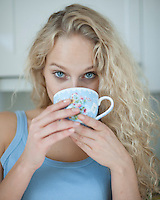 Portrait of woman drinking tea in kitchen