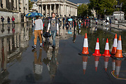 Pedestrians enjoy a brighter spell again after a heavy autumnal downpour in Trafalgar Square in central London, on 1st October 2019, in London, England.