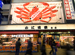 Large crab outside seafood restaurant at night in Dotonburi nightlife district of Osaka Japan