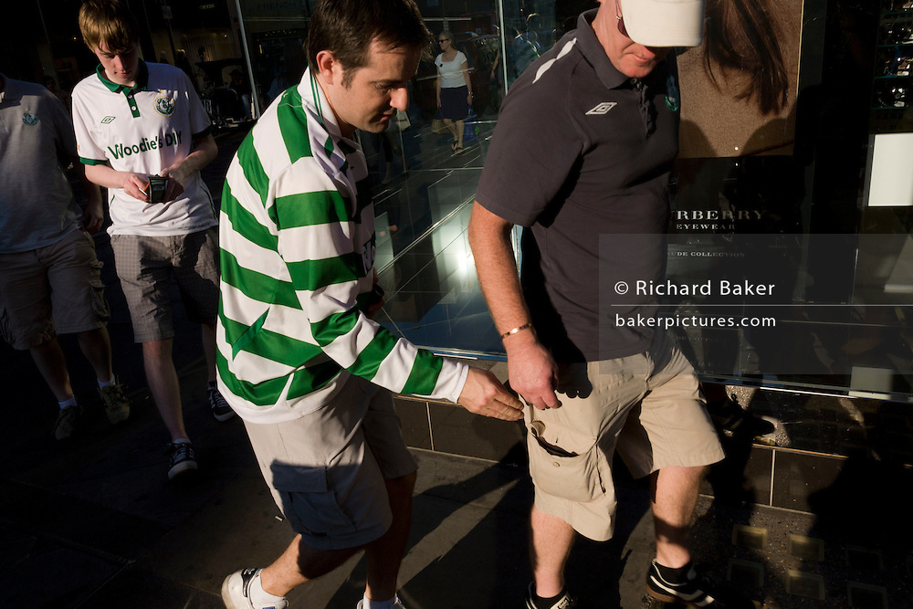 Football supporter mates mess around in a London street before going on to watch their team's match elsewhere in the capital. But this man in the green stripes of his team is NOT a pickpocket as might be suggested on first look. He reaches into the unbuttoned pocket of the older-looking man in shorts. But recaptioning this picture to suggest he is a street criminal might be thought libelous, giving this brief moment a misinterpretation and misrepresentation.