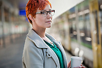 Portrait of businesswoman holding cup of coffee while waiting for train