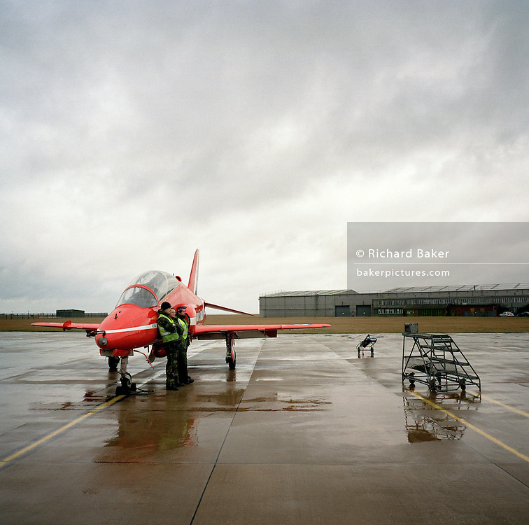 Engineering ground staff of the Red Arrows, Britain's RAF aerobatic team shelter from weather on airfield apron.