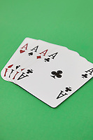Four aces playing cards over green surface