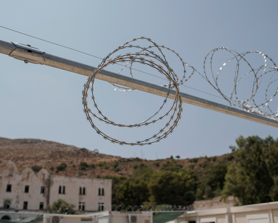 A barbed wired gate that separates the different communities of migrants and refugees into sections at the First Reception Centre (Hot-Spot) of Leros, Greece. <br />