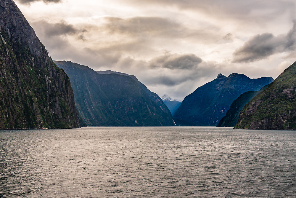 A dark and narrow passageway through a New Zealand Fiord under threatening skies.