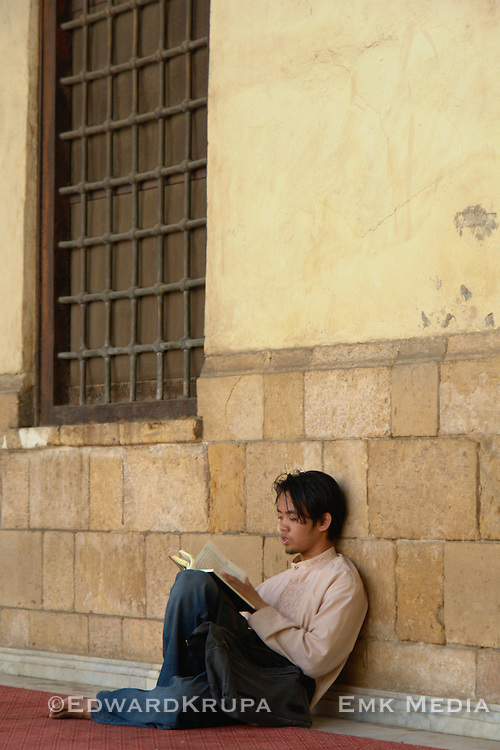 Young man sits and reads the Koran in the Al-Azhar Mosque in Cairo.