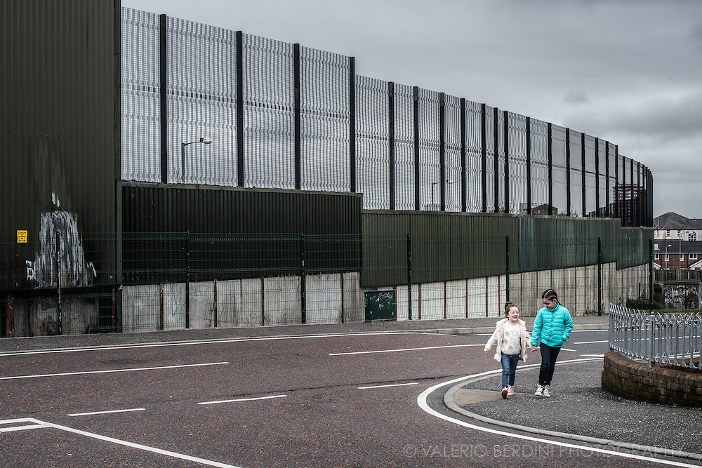 Two girls walk along the Peace Line, the wall that once separated Irish Nationalists and Unionists in Belfast. Still in place in most parts of West Belfast, the gates are now open.