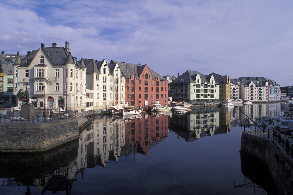 Europe, Norway. Renovated warehouses reflected in harbor of downtown Ålesund