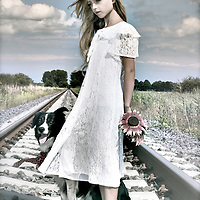 Female youth outdoors holding sunflowers standing on train track in summer with sheep dog