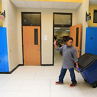 Tupelo Middle School student Tony Mays waves to other students as he pulls the recycling bin down the hallway so he and his classmates can begin making their ounds to pick up all the paper recycling.