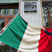 VENICE, ITALY - MARCH 17:  Two old partisans prepare their flag under a stone remembering martyrs of the Risorgimento on the day of the celebrations for the 150th anniversary of Italy's unification on March 17, 2011 in Venice, Italy. Events in various Italian cities will celebrate the 150th anniversary of Italy's unification until the end of the year. National Festivity begins on March 17.