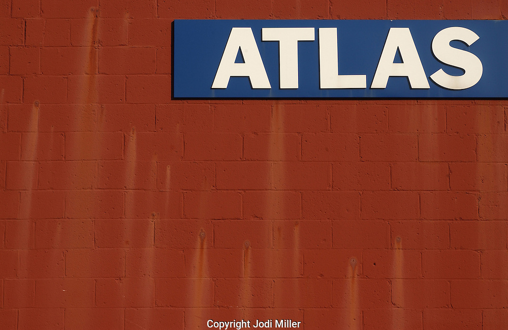 The word Atlas on the side of a red cinder block building.