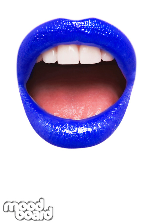 Close-up view of female wearing dark blue lipstick with mouth open over white background