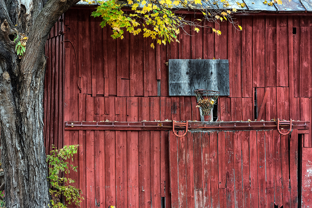 An neglected basketball hoop mounted on a rural red barn, New York, USA.