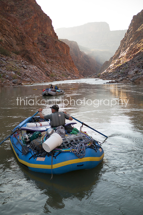 View from behind of man rowing raft on Colorado River, Grand Canyon, AZ