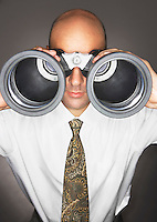 Balding Middle-aged businessman looking through large binoculars