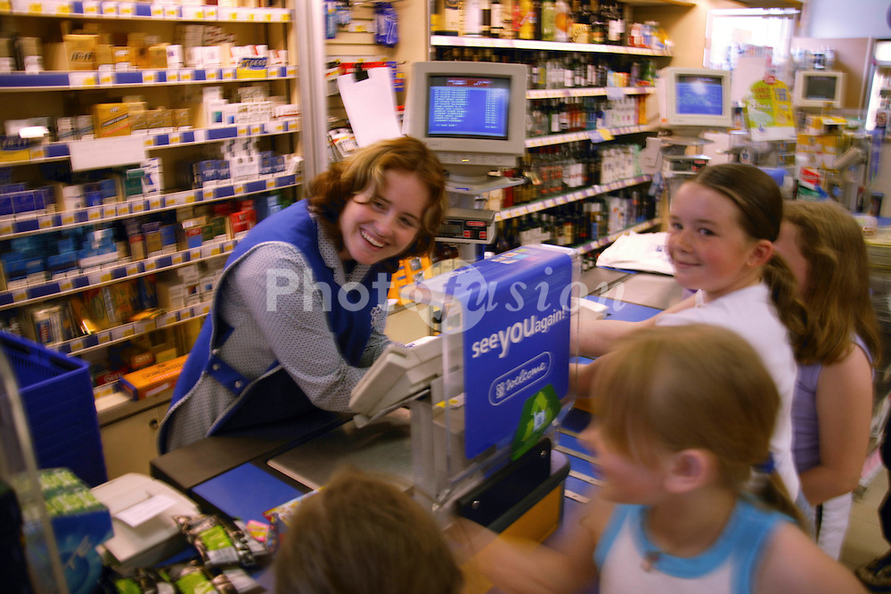 Shop assistant with learning disability serving group of young children at supermarket checkout,