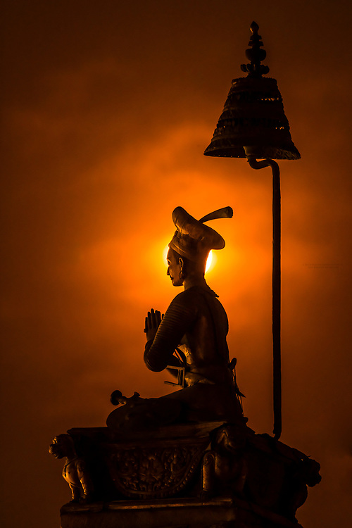 The statue of King Bhupatindra Malla silhouetted by a full moon, Durbar Square, Bhaktapur, Kathmandu Valley, Nepal.