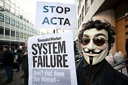 """© licensed to London News Pictures. London, UK 11/02/2012. A protester holds """"Stop ACTA"""" and """"System Failure"""" signs at the demonstration against the anti-privacy law ACTA, outside British Music House in central London. Photo credit: Tolga Akmen/LNP"""