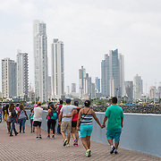 People enjoying the waterfront boardwalk in Casco Viejo in Panama City, Panama, with the modern skyscrapers of Punta Paitilla in the background.