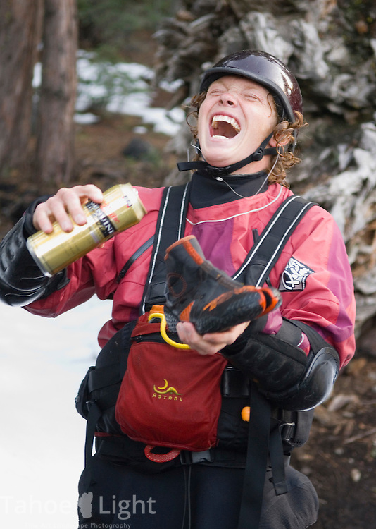 Local kayaker at Patagonia employee Corey Volt prepares to drink a beer out of his bootie in penance after severly blowing his line and going over East meets West, a 25 foot waterfall on the SF of the Yuba River near Donner Summit upside down.