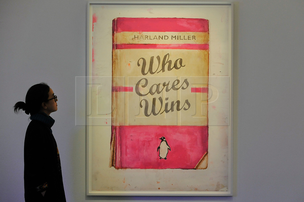 """© Licensed to London News Pictures. 12/10/2017. London, UK.  A staff member views """"Who Cares Wins"""", 2017, by Harland Miller (Est. GBP20-25k) at a preview of artworks for the """"Art for Grenfell"""" auction taking place at Sotheby's, New Bond Street, on 16 October.  Leading contemporary artists have agreed to donate works to the auction, the proceeds of which will be divided equally amongst the 158 surviving families of the Grenfell Tower fire by the Rugby Portobello Trust charity. Photo credit : Stephen Chung/LNP"""