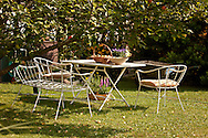 Garden table and chairs next to apple tree, Munich, Bavaria, Germany