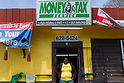 """UNIONTOWN, AL – MARCH 21, 2014: Alisha Reed stands in front of the Money Tax store where she prepares taxes for customers. Reed went through mandatory training for her job in Selma, Alabama before she could begin work preparing taxes for customers. """"The majority of them get money back,"""" Reed said. Money Tax has several locations in the state of Alabama and serves a predominantly poorer segment of the state's population from December through April each year. During tax season, many locally owned tax preparation services rake in large profits by promising high tax returns to their customers. CREDIT: Bob Miller for The New York Times"""