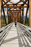 Backpacker crossing foot bridge over Placer River in Chugach National Forest in Southcentral Alaska. Summer. Afternoon.