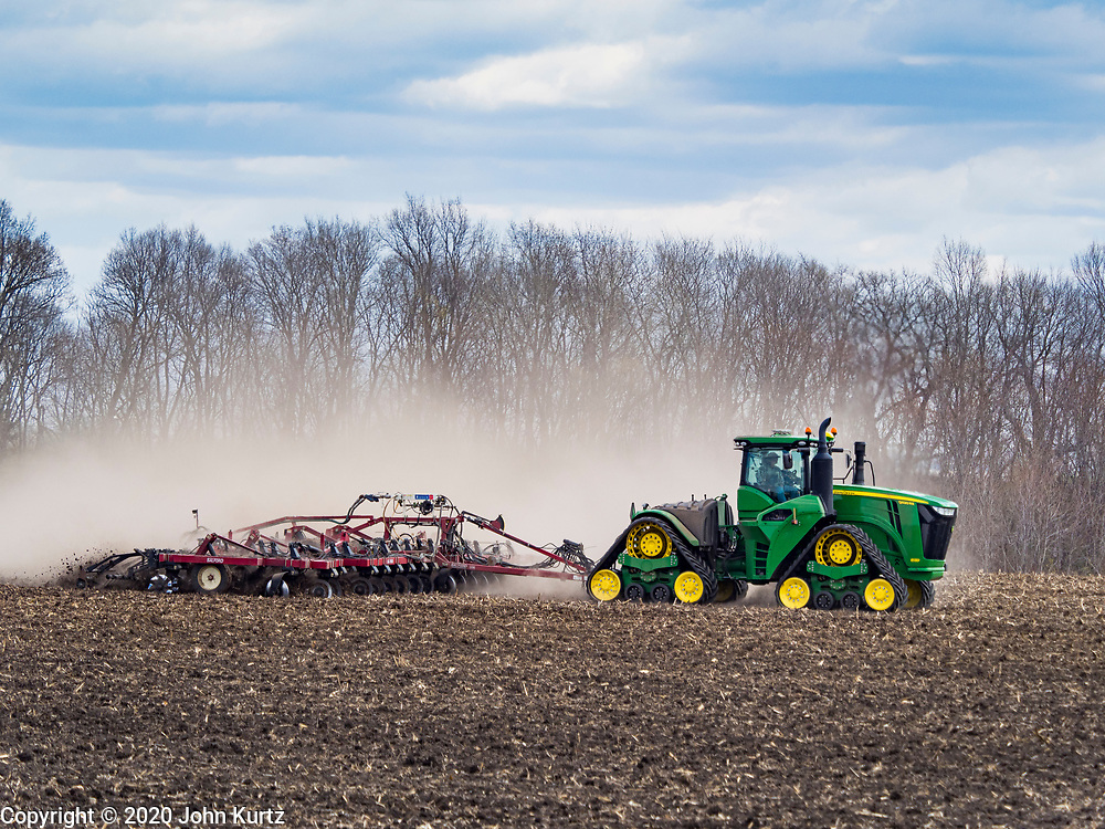 "20 APRIL 2020 - BOUTON, IOWA: A farmer tills a field near Bouton. Iowa farmers are prepping their fields for the 2020 season. The relatively mild winter and dry spring has allowed farmers to get into their fields 1 - 2 weeks earlier than last year. Farmers and agricultural workers are considered ""essential"" workers in Iowa and not subjected to the coronavirus restrictions nonessential workers are. Farmers usually work by themselves, and social distancing guidelines have not impacted them as much as it has workers in Iowa's cities.      PHOTO BY JACK KURTZ"